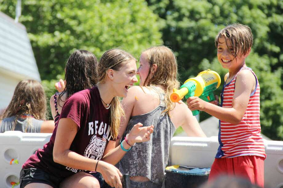 """In a last minute effort to beat the heat, a number of floats used water guns to """"cool down"""" the onlookers during Thursday's Fourth of July parade in downtown Port Austin. Here, a couple of parade participants smile and laugh after dousing the crowd with water. Photo: Andrew Mullin/Huron Daily Tribune"""