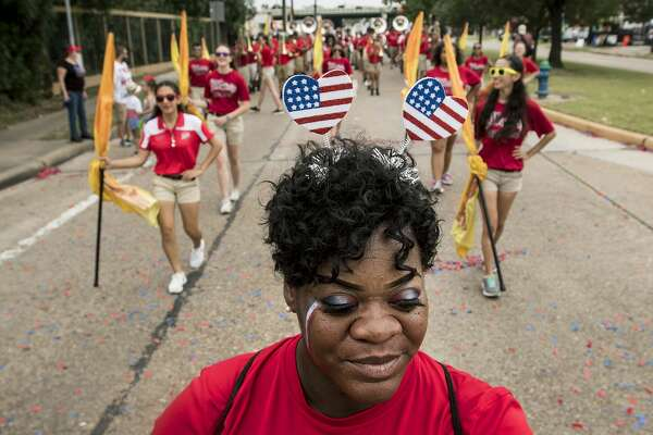 Joyce Joseph, a parent volunteer, walks in front of the Waltrip High School Band as they march during the 20th Annual Lindale Park 4th of July Parade on Thursday, July 4, 2019, in Houston.