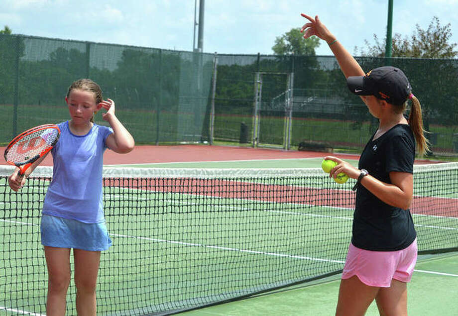 Edwardsville assistant coach Emily Cimarolli, right, instructs Junior Team Tennis player Estelle Borden during a recent practice at the EHS Tennis Center. Edwardsville has 46 JTT players on four teams this summer. Photo: Scott Marion/The Intelligencer