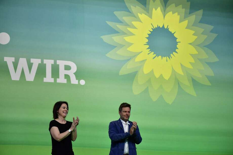 (FILES) In this file photo taken on November 10, 2018 Leaders of the German Green party, Robert Habeck (R) and Annalena Baerbock applaud on stage during the party's congress in Leipzig, eastern Germany where delegates elected candidates for next years European elections. - With the numbers suggesting that Germany's highest office may be within reach for the Greens, the buzz is not whether the party could fill the seat at the chancellery but which of its two co-chiefs -- Annalena Baerbock and Robert Habeck -- could seize the top job. (Photo by Tobias SCHWARZ / AFP)TOBIAS SCHWARZ/AFP/Getty Images Photo: TOBIAS SCHWARZ / AFP or licensors