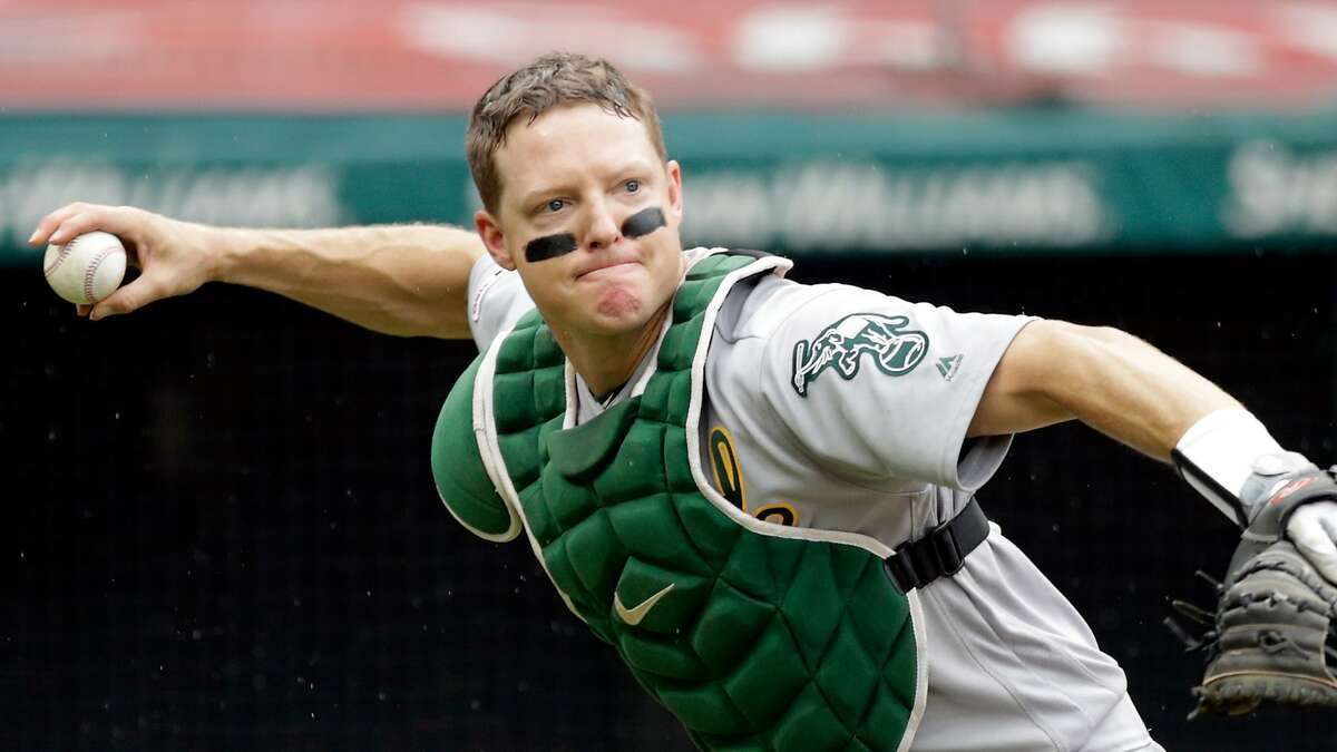 Oakland Athletics' Nick Hundley throws out Cleveland Indians' Leonys Martin at first base in the fourth inning of a baseball game, Wednesday, May 22, 2019, in Cleveland. (AP Photo/Tony Dejak)