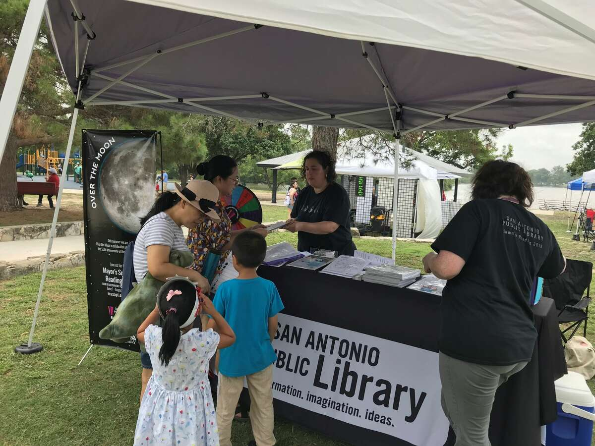 Julia Lazarin, early childhood services specialist for San Antonio Public Libraries, explains the Over the Moon summer reading program at the Woodlawn Lake Fourth of July celebration.