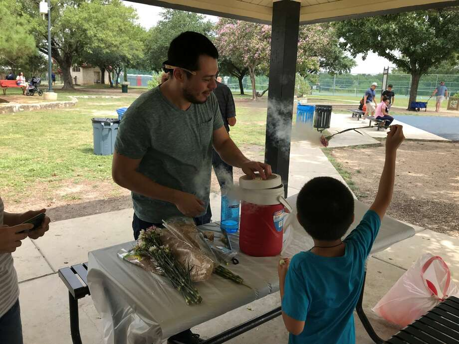 Frank Herkules demonstrates how liquid nitrogen quickly freezes the water on flower petals at the Woodlawn Lake Fourth of July celebration. Herkules said the frozen water causes the petals to change texture and become very fragile. Photo: Austin Taylor