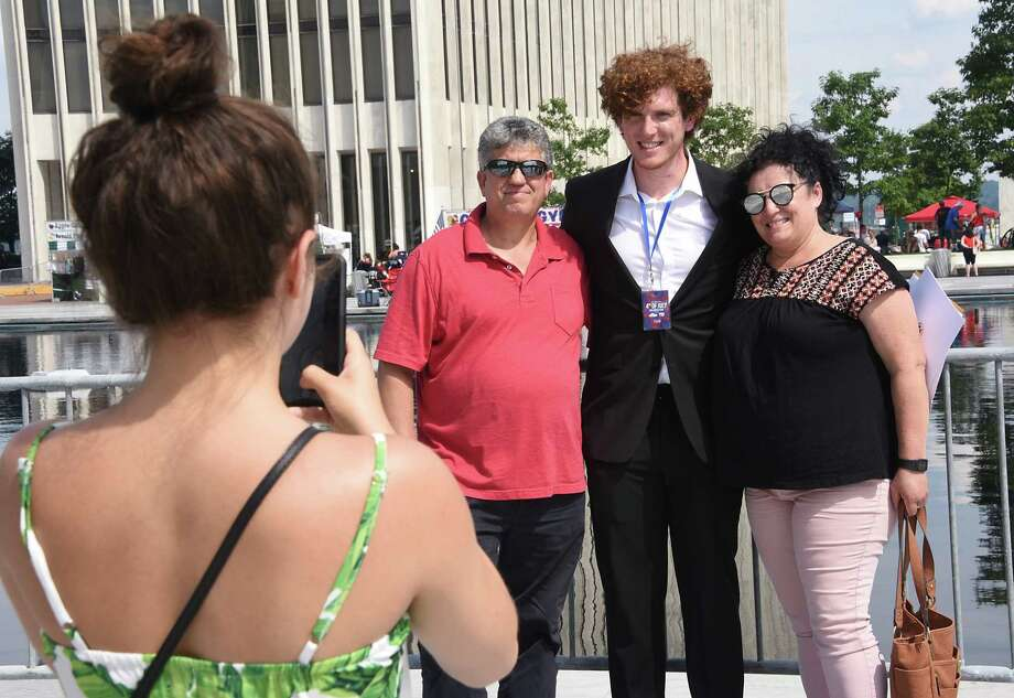 Alexa Juran, left, takes a photo of her boyfriend Dhimiter Cobani of Albania, center, and his parents Vasil Cobani and Mirela Cobani, right, after Dhimiter received his certificate of citizenship at the Naturalization Ceremony at the Empire State Plaza on Thursday, July 4, 2019 in Albany, N.Y. The ceremony took place during the 44th annual Independence Day celebration at the plaza. (Lori Van Buren/Times Union) Photo: Lori Van Buren, Albany Times Union / 20047377A