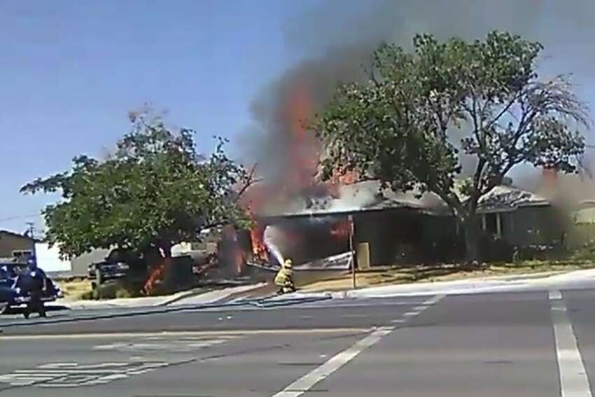 In this image taken from video provided by Ben Hood, a firefighter works to extinguish a fire on July 4, 2019, following an earthquake in Ridgecrest.