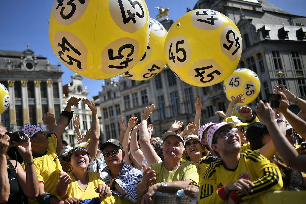 Cyclism fans play with yellow inflatable balloons as they wait for the Tour de France 2019 teams presentation at the Grand-Place - Grote Markt Square in Brussels on July 4, 2019, two days prior to the start of the 106th edition of the Tour de France cycling race. - On Saturday, July 6, the 106th edition of the Tour de France will start with a 194.5km stage in the region of Brussels, 100 years after the introduction of the yellow jersey and 50 years after Belgian legend Eddy Merckx won his first Tour. (Photo by Marco Bertorello / AFP)MARCO BERTORELLO/AFP/Getty Images