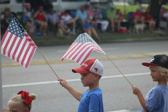 Two flag-waving children await the arrival of the parade and the city's 124th celebration.