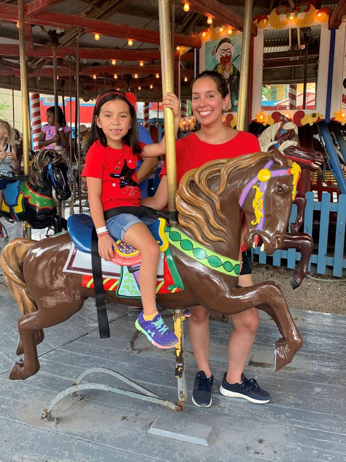 Meghan Heinz and Mia Valenzuela, 5, enjoy the carousel at Kiddie Park on its last day at the Broadway location on Thursday.