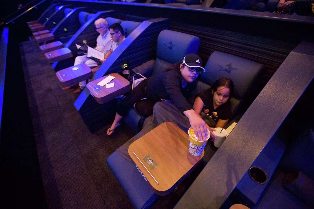 Christina Covenas reaches over her sister Chloe, 8, for popcorn during the previews before Toy Story 4 at Star Cinema Grill in Richmond, Friday, June 21, 2019. Movie theaters in the Houston area are upping the ante of amenities like offering privacy pods with blankets to compete with ever-improving home theater systems.