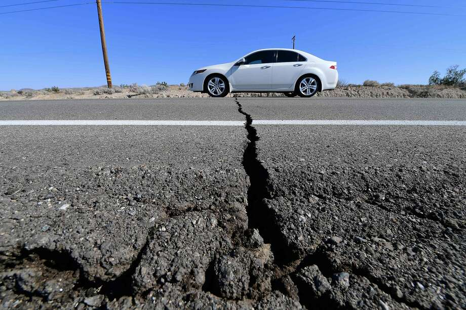 A car drives past a crack in the road after a 6.4-magnitude earthquake in Ridgecrest, California, on July 4, 2019. - Southern California was rocked by a 6.4-magnitude earthquake Thursday morning, the US Geological Survey said, with authorities warning that the temblor, the largest in two decades, might not be the day's last. (Photo by FREDERIC J. BROWN / AFP)FREDERIC J. BROWN/AFP/Getty Images Photo: Frederic J. Brown / AFP / Getty Images