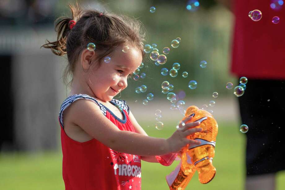 Liberty McCormack, 2, sprays a bubble gun towards herself during the the 22nd annual Red, Hot and Blue festival July, 4, 2019 at Town Green Park in The Woodlands. McCormack was also celebrating her second birthday. Photo: Cody Bahn, Houston Chronicle / Staff Photographer / © 2019 Houston Chronicle