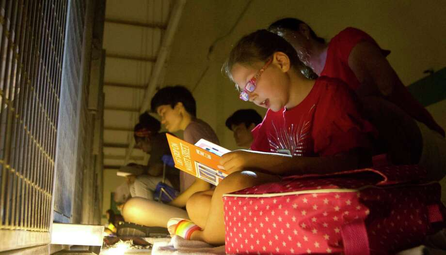 Jaylin Bucolo, of Montgomery, reads to dogs with the help of her mother, Jennifer, at the Montgomery County Animal Shelter during the Fourth of July to help calm them in the already stressful environment of the shelter, Thursday, July 4, 2019, in Conroe. More than 50 volunteers read with dogs and Lone Star Animal Welfare League offered free micro chipping for dogs and cats. Photo: Jason Fochtman,  Houston Chronicle / Staff Photographer / Houston Chronicle