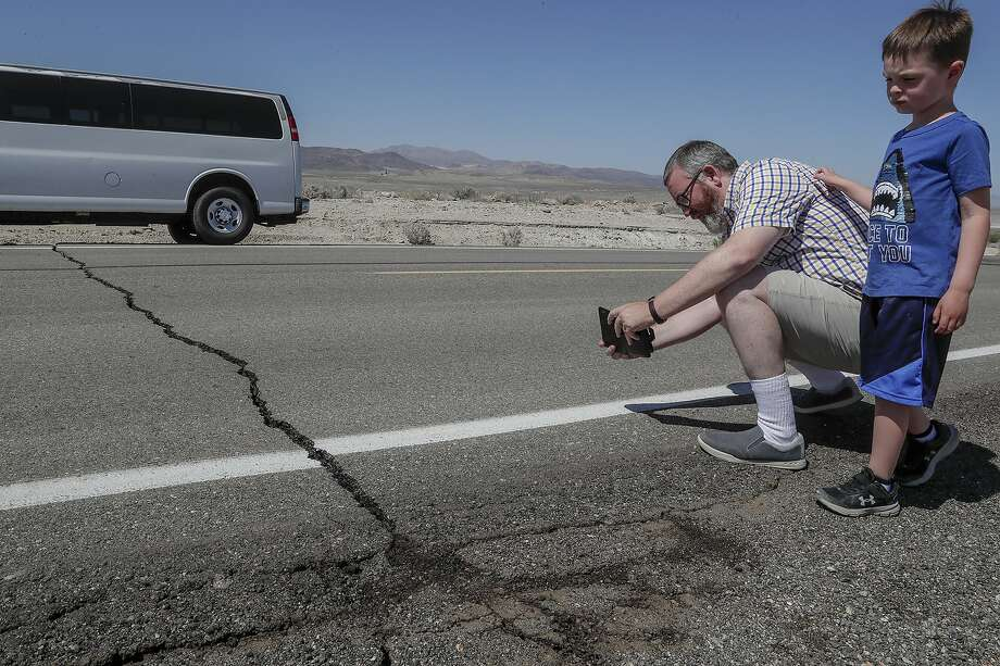 Andy Randolph and his son William stop for photos of a crack in California State Route 178 hours after a 6.4 magnitude earthquake struck the Searles Valley area in southern California on Thursday, July 4, 2019. Photo: Robert Gauthier, TNS
