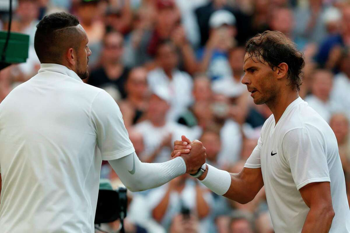 Spain's Rafael Nadal (R) shakes hands with Australia's Nick Kyrgios (L) after Nadal won their men's singles second round match on the fourth day of the 2019 Wimbledon Championships at The All England Lawn Tennis Club in Wimbledon, southwest London, on July 4, 2019. (Photo by Adrian DENNIS / AFP) / RESTRICTED TO EDITORIAL USEADRIAN DENNIS/AFP/Getty Images