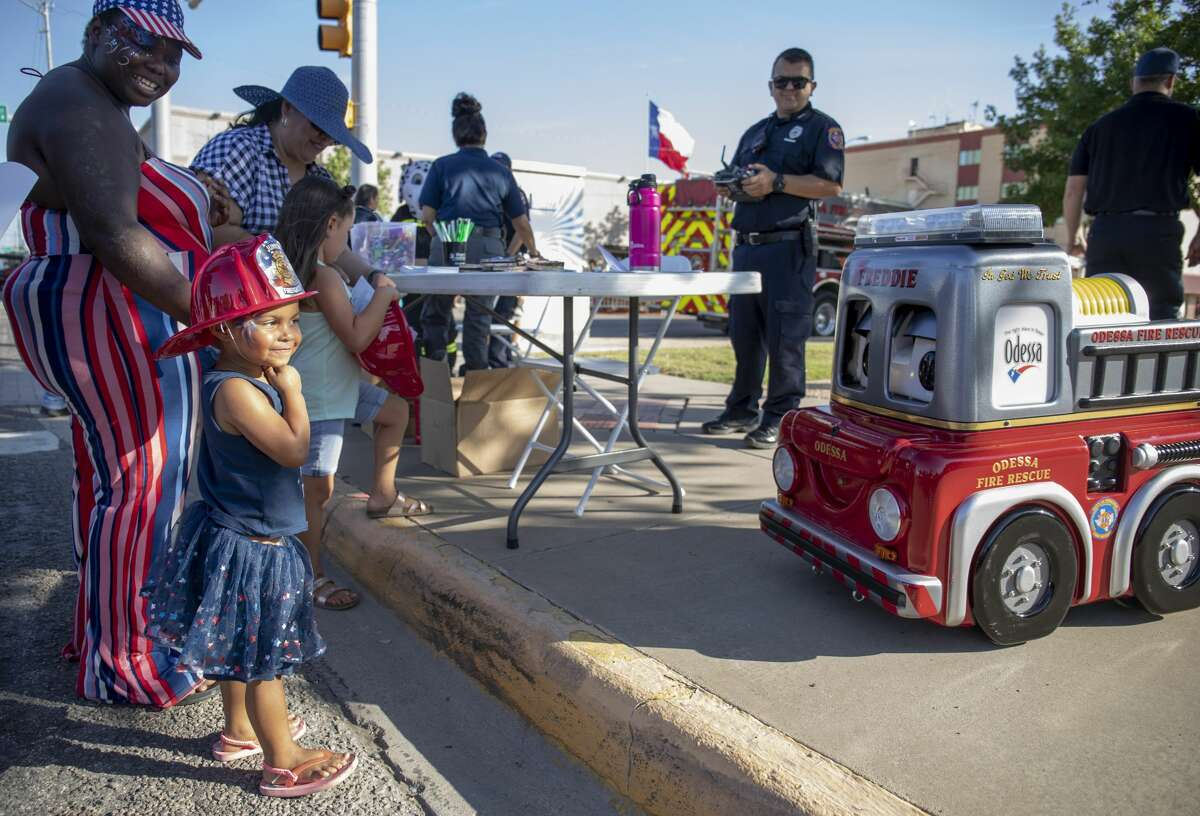Jordan Renee Green watches Freddie a miniature fire engine Odessa Fire Rescue controls during the 24th annual Firecracker Fandango on Thursday, July 4, 2019 in downtown Odessa Jacy Lewis/Reporter-Telegram
