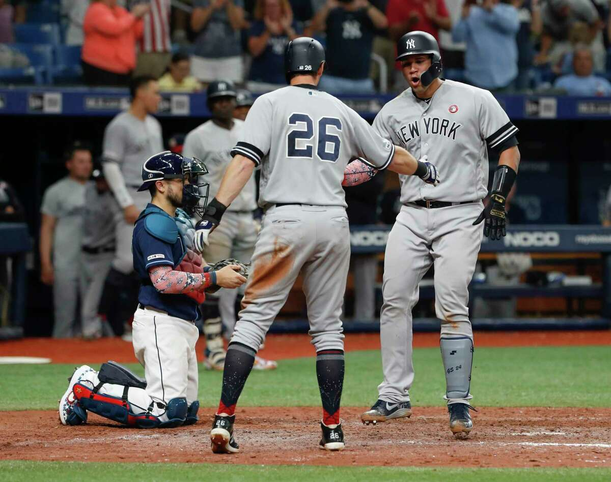 New York Yankees' Gary Sanchez, right celebrates with teammate DJ LeMahieu after hitting a three-run home run against the Tampa Bay Rays during the 10th inning of a baseball game Thursday, July 4, 2019, in St. Petersburg, Fla. (AP Photo/Scott Audette)