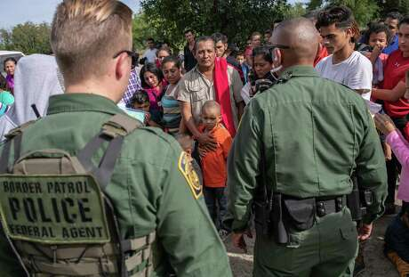 LOS EBANOS, TEXAS - JULY 02: U.S. Border Patrol agents watch over immigrants after taking them into custody on July 02, 2019 in Los Ebanos, Texas. Hundreds of immigrants, most from Central America, turned themselves in to border agents after rafting across the Rio Grande from Mexico to seek political asylum in the United States. (Photo by John Moore/Getty Images)