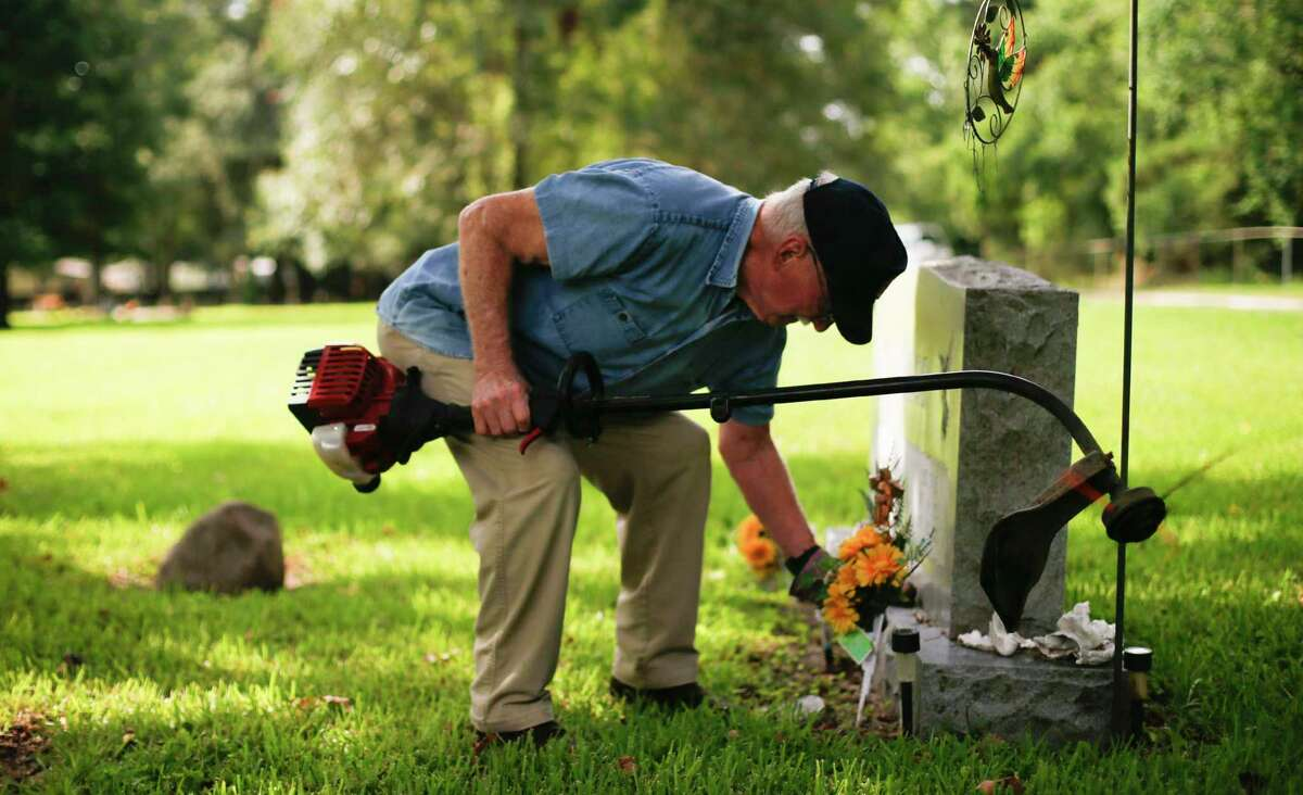 Linney Cemetery volunteer, Henry Buxton, fixes flowers on a tombstone at the Dayton, Texas cemetery on Tuesday, July 2, 2019. Buxton took down the fence that separated Linney from Acie Cemetery.