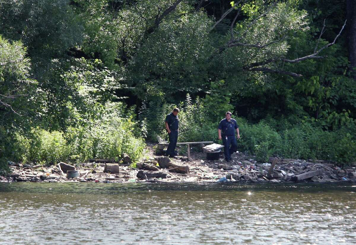 Law enforcement investigate the banks of the Passaic River in Clifton, N.J. where a body originally from Stamford was discovered.