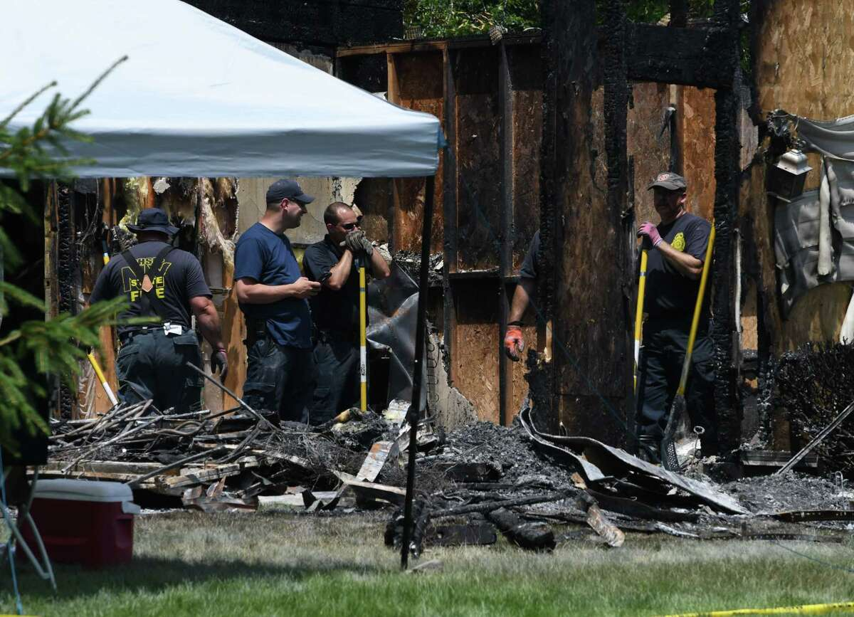 Investigators search for clues in the cause of a Marne Street fire on Friday, July 5, 2019, in Colonie, N.Y. The fire began Thursday in the garage. (Will Waldron/Times Union)