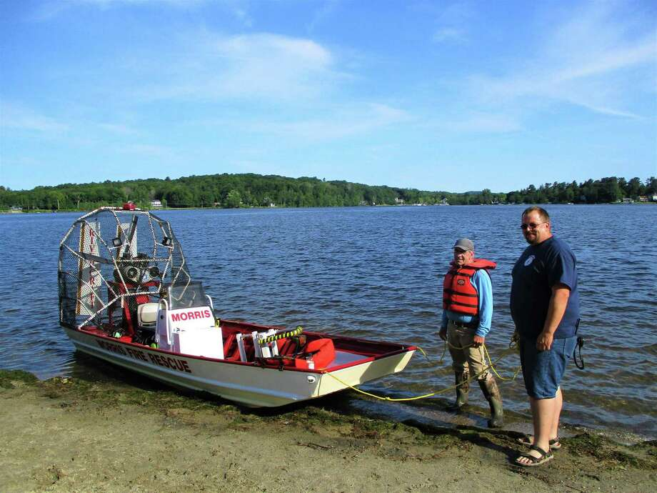 Steve Maughmer and George Humphrey III stand ready with the Morris Fire Company rescue airboat. Photo: Jo Ann Jaacks / For Hearst Media Connecticut