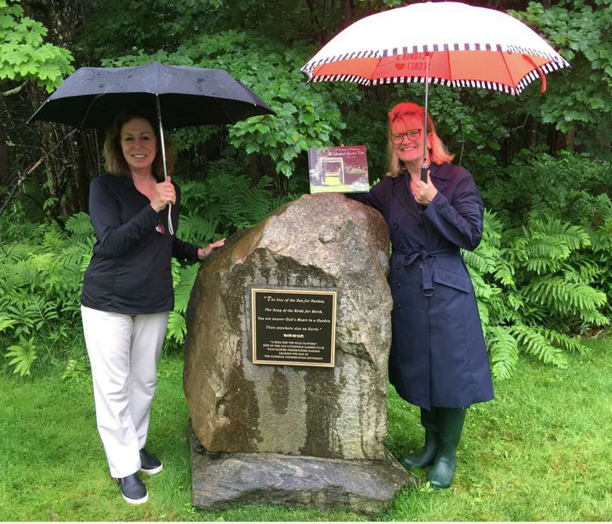 Maryanne McNeill and Jane Hinkel, project committee co-chairpersons of the Litchfield Garden Club, stand by the newly dedicated monument, and show the book,