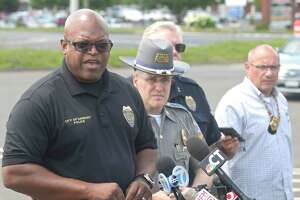 Police Chief Patrick Ridenhour, left, speaks at a press conference, in the I-84 exit 2 commuter parking lot, about an officer involved shooting that happened Wednesday morning in the area. July 3, 2019, in Danbury, Conn.