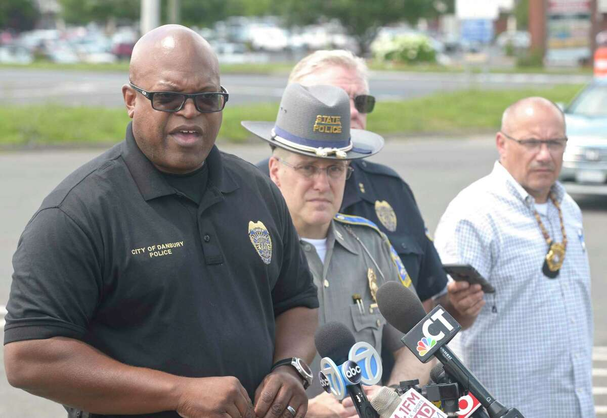 Police Chief Patrick Ridenhour ,left, speaks at a press conference, in the I-84 exit 2 commuter parking lot, about an officer involved shooting that happened Wednesday morning in the area. July 3, 2019, in Danbury, Conn.