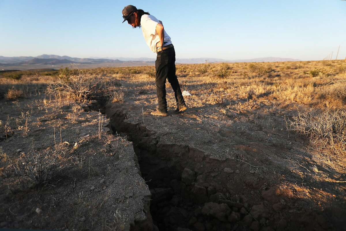 A local resident inspects a crack in the earth after a 6.4 magnitude earthquake struck the area on July 4, 2019 near Ridgecrest.
