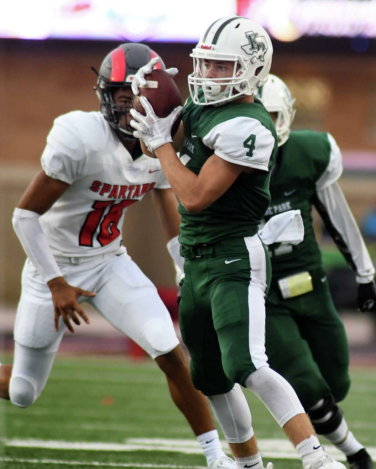 Kingwood Park junior wide receiver Canen Adrian (4) finishes a catch against a Porter defender in the second quarter of their District 9-5A matchup at Turner Stadium in Humble on Sept. 29, 2018.