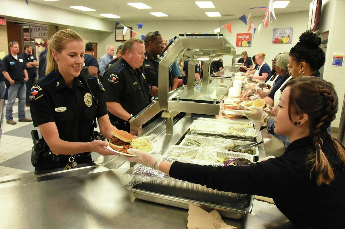 CFISD police officer Rebecca Sosa receives a BBQ plate prepared by CFISD transportation department employees at the CFPD / Security Department Appreciation Lunch on Oct. 10 at Cy-Fair High School.