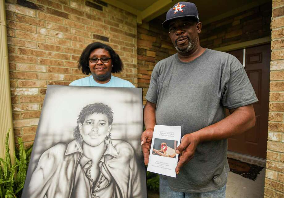 Nataujia and Mark DeJohn Sr. pose while holding a drawing of Mark's late mother Russell Jean DeJohn Hampton and a ceremony booklet from the National Memorial to Fallen Educators at their house in Port Arthur on Tuesday. Hampton was shot and killed in 1988 as she was driving a school bus in Port Arthur. The drawing was given to Mark by his brother Timothy Hampton, who works in a prison in Huntsville, after Hampton himself was given the art by an inmate who signed the drawing as J. Hurd. Photo taken on 07/02/19. Ryan Welch/The Enterprise Photo: Ryan Welch, Beuamont Enterprise / The Enterprise / © 2019 Beaumont Enterprise