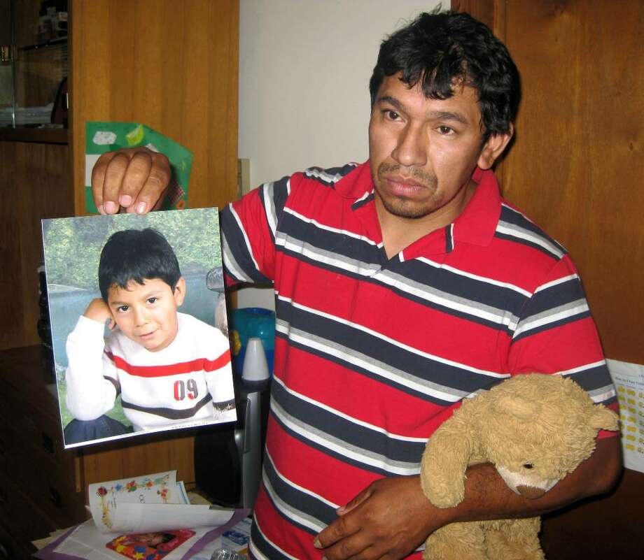 Carlos Zhunio holds up a photo and favorite toy of his 4-year-old son, Eric, who died from injuries after a pick-up truck hit him on Thursday, July 29, 2010. The truck hit Eric outside of his home on Stevens Street. Photo: Vinti Singh / The News-Times