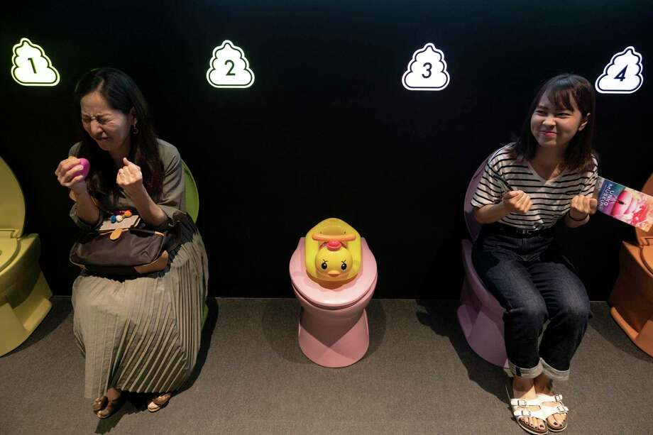 In this Tuesday, June 18, 2019, photo, two women jokingly motion to give a push while sitting on colorful toilet bowls at the Unko Museum in Yokohama, south of Tokyo. In a country known for its cult of cute, even poop is not an exception. A pop-up exhibition at the Unko Museum in the port city of Yokohama is all about unko, a Japanese word for poop. The poop installations there get their cutest makeovers. They come in the shape of soft cream, or cupcake toppings. (AP Photo/Jae C. Hong) Photo: Jae C. Hong, STF / Associated Press / Copyright 2019 The Associated Press. All rights reserved.