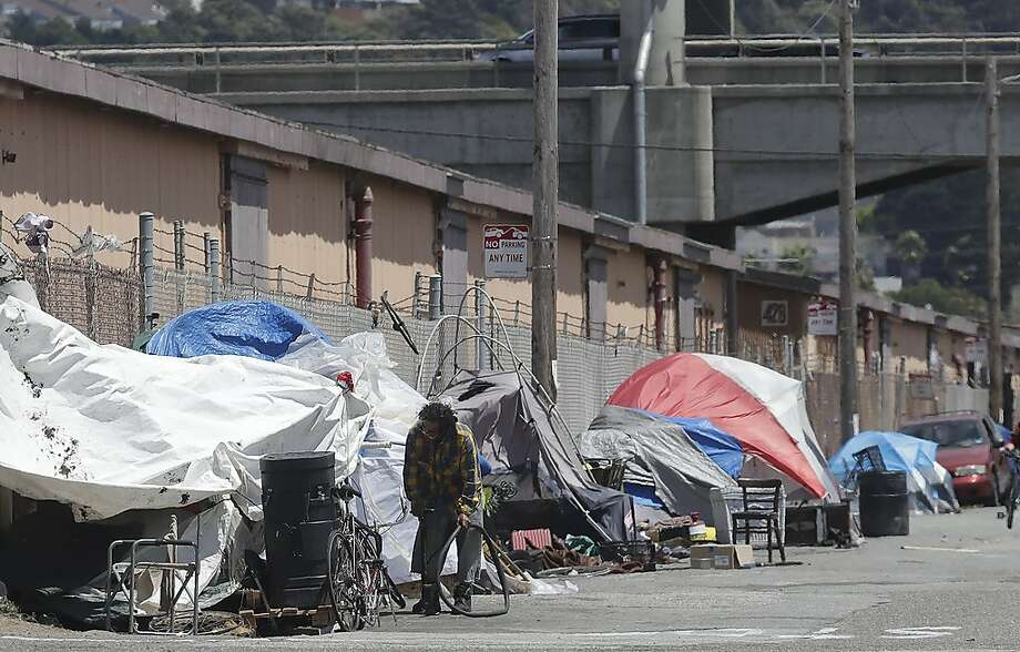 This Thursday, June 27, 2019, photo shows a man holding a bicycle tire outside of a tent along a street in San Francisco. A federally mandated count of homeless in San Francisco increased 17% in two years, driven in part by a surge of people living in RVs and other vehicles. (AP Photo/Jeff Chiu) Photo: Jeff Chiu / Associated Press