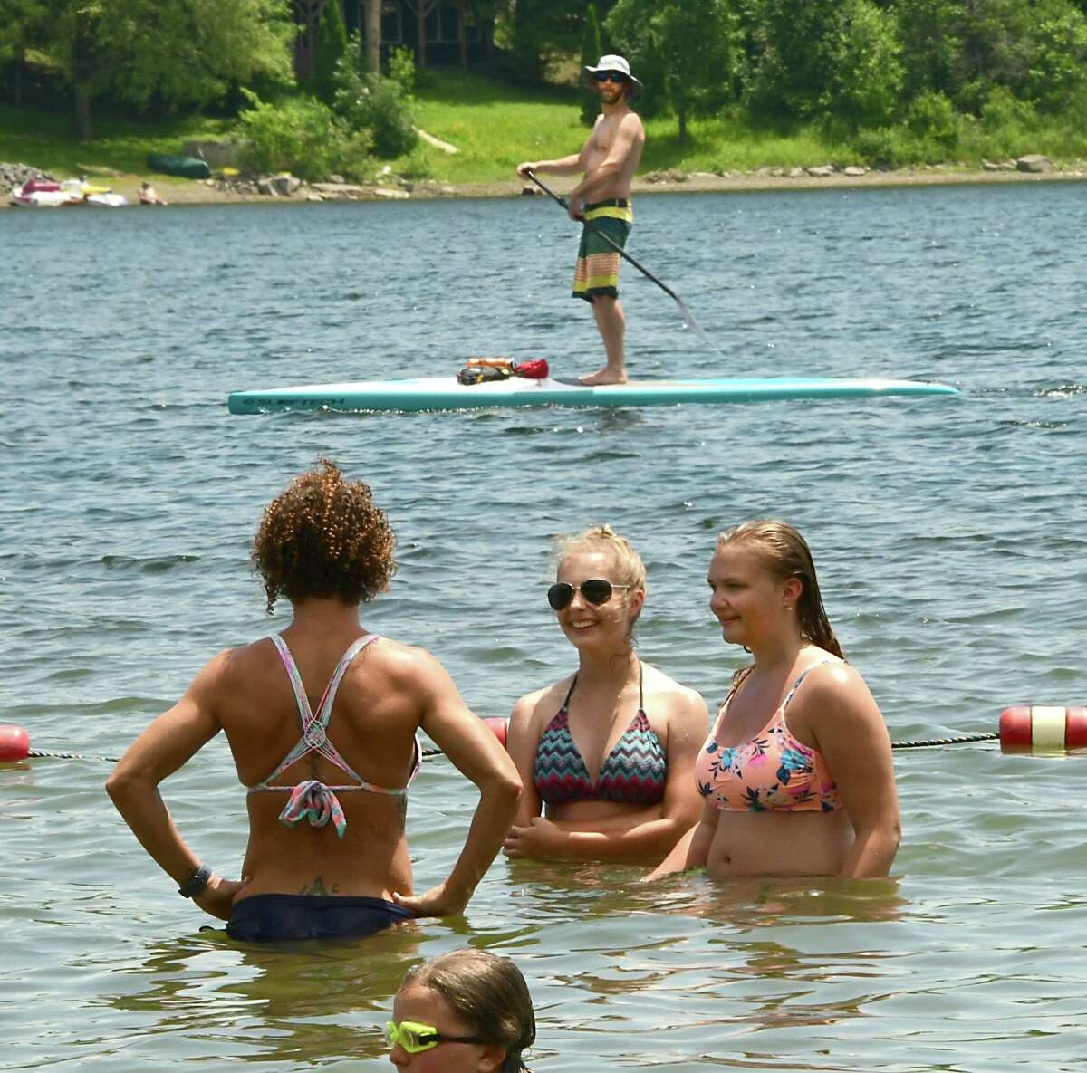 A man goes by the beach on a stand-up paddle board at Thompson's Lake Campground on Friday, July 5, 2019, East Berne, N.Y. (Lori Van Buren/Times Union)