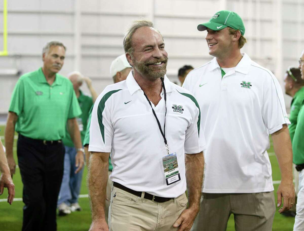 In this Sept. 6, 2014 photo shows Chris Cline, center, Chad Pennington, right, and Mike D'Antoni, left, arrive as Marshall University dedicates the new indoor practice facility as the Chris Cline Athletic Complex in Huntington, W.Va. Police in the Bahamas say a helicopter flying from Big Grand Cay island to Fort Lauderdale has crashed, killing seven Americans on board. None of the bodies recovered from the downed helicopter have been identified, but police Supt. Shanta Knowles told The Associated Press on Friday, July 5, 2019, that the missing-aircraft report from Florida said billionaire Chris Cline was on board. (Sholten Singer/The Herald-Dispatch via AP)