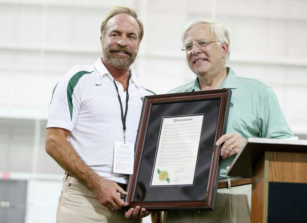 In this Sept. 6, 2014 photo, President Stephen Kopp, right, congratulates Chris Cline as Marshall University dedicates the new indoor practice facility as the Chris Cline Athletic Complex in Huntington, W.Va. Police in the Bahamas say a helicopter flying from Big Grand Cay island to Fort Lauderdale has crashed, killing seven Americans on board. None of the bodies recovered from the downed helicopter have been identified, but police Supt. Shanta Knowles told The Associated Press on Friday, July 5, 2019, that the missing-aircraft report from Florida said billionaire Chris Cline was on board. (Sholten Singer/The Herald-Dispatch via AP)