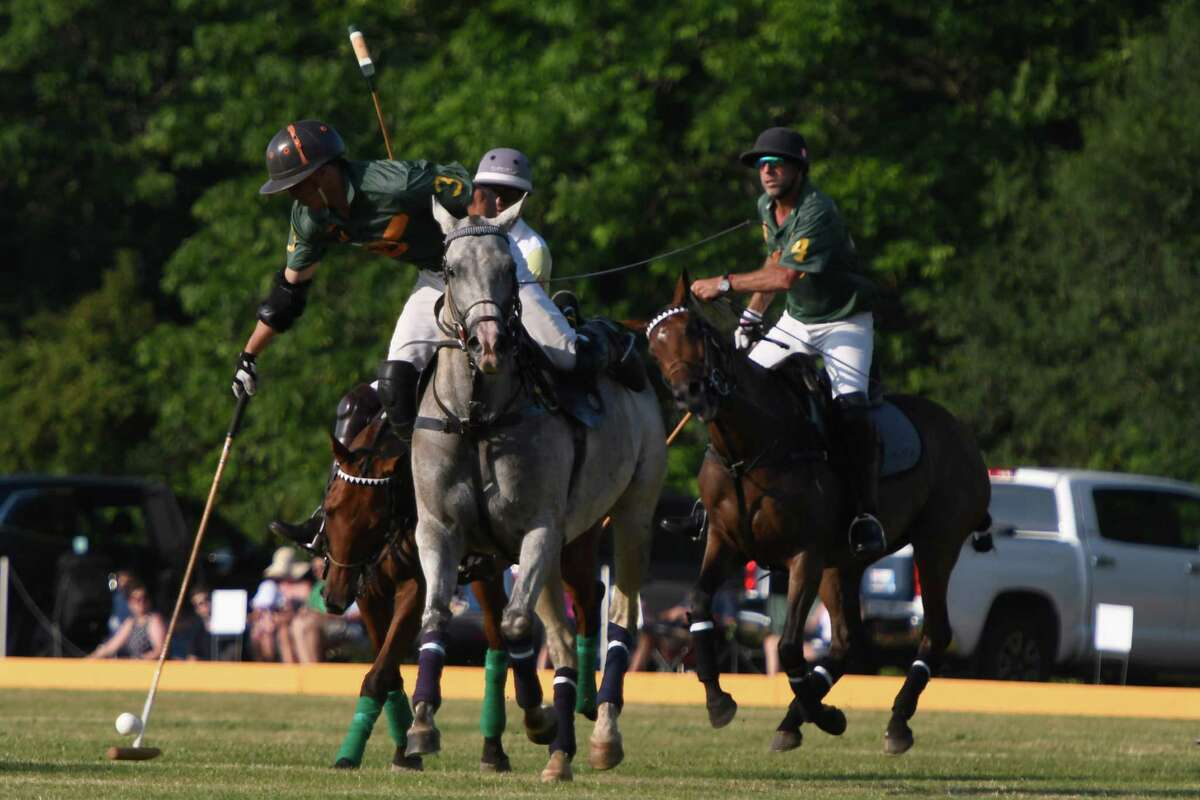RoseView Farms's Bautista Crotto leans over the side of his mount to hit the ball during the season opening match at Saratoga Polo Club on Friday, Jul. 5, 2019 in Greenfield, N.Y. (Jenn March, Special to the Times Union )
