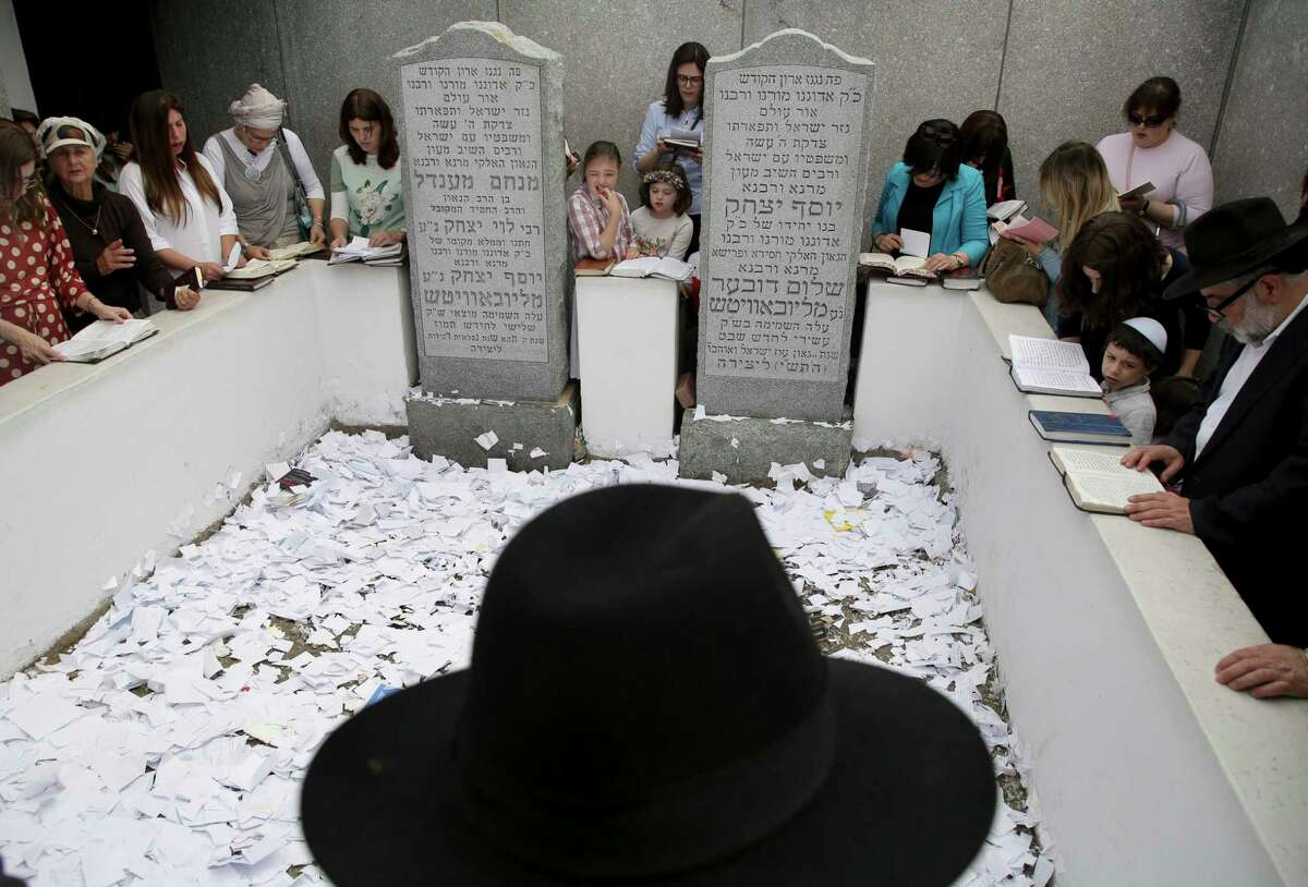 In this July 2, 2019 photo, people pray at the gravesite of Rabbi Menachem M. Schneerson in the Queens borough of New York. Men and women, young and old, make their way from around the city, the country and the world to this unassuming site, the burial place of Rabbi Menachem Mendel Schneerson, to pay their respects to the life and teachings of the revered Jewish leader of the Chabad-Lubavitch movement who died twenty-five years ago in June 1994. (AP Photo/Seth Wenig)