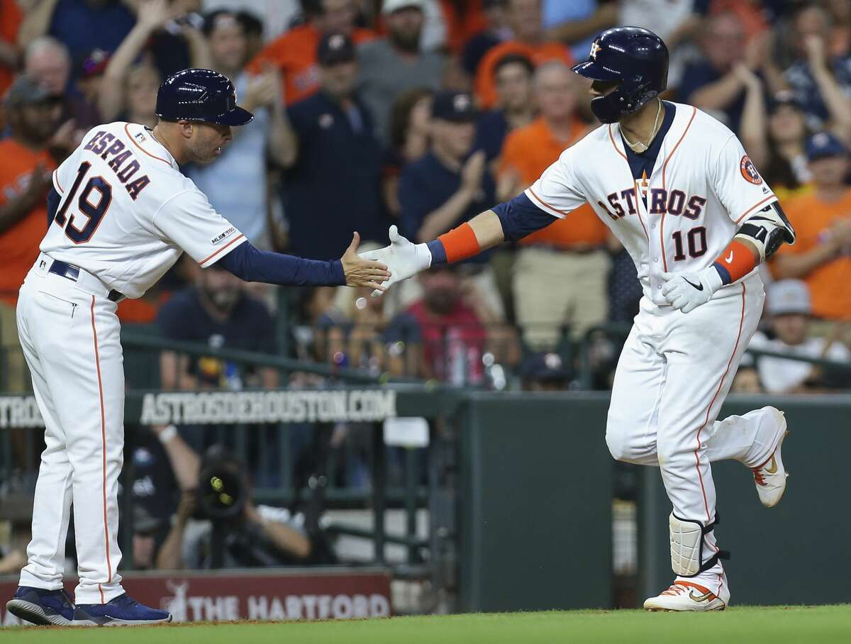 Houston Astros first baseman Yuli Gurriel (10) celebrates his two-run home run with third base coach Joe Espada (19) during the bottom eighth inning of the MLB game against the Los Angeles Angels against the Los Angeles Angels at Minute Maid Park on Friday, July 5, 2019, in Houston.
