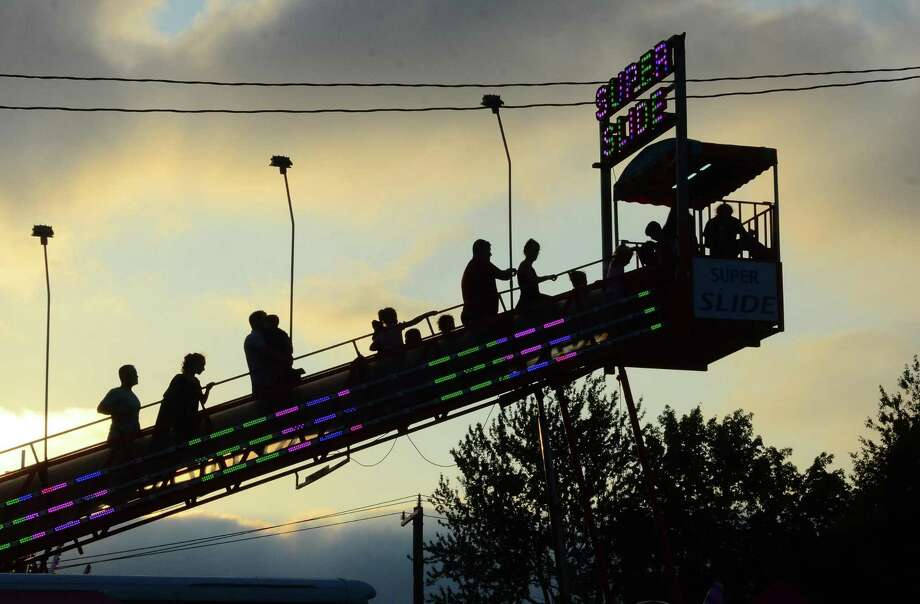 People climb the stairs to the top of the Super Slide during the annual Monroe Firemen's Carnival in Monroe, Conn., on Friday July 5, 2019. There is no admission or parking fee and the rides are paid via tickets or a ride-all-night bracelet. The carnival continues on Saturday from 6:00 PM - 11:00 PM. Photo: Christian Abraham / Hearst Connecticut Media / Connecticut Post