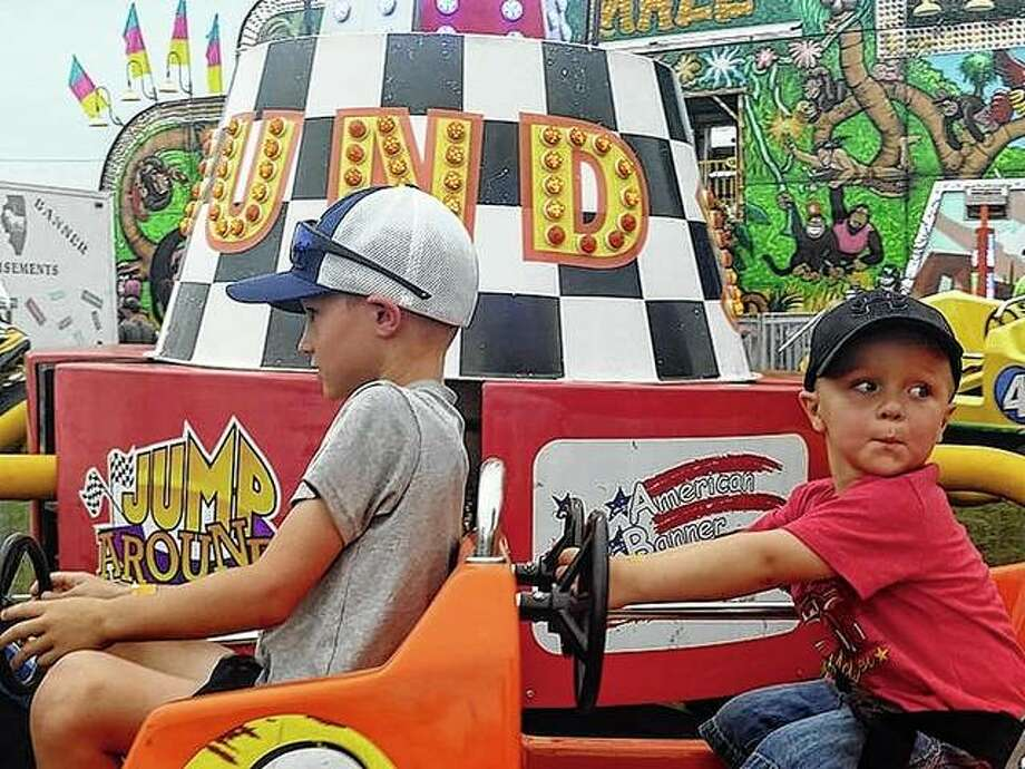 Isaac Ferguson (left), the son of Chad and Ashley Ferguson, and Brooks Richmiller, 3, the son of Cassie and J.P. Richmiller ride a car attraction at the Schuyler County Fair Friday.