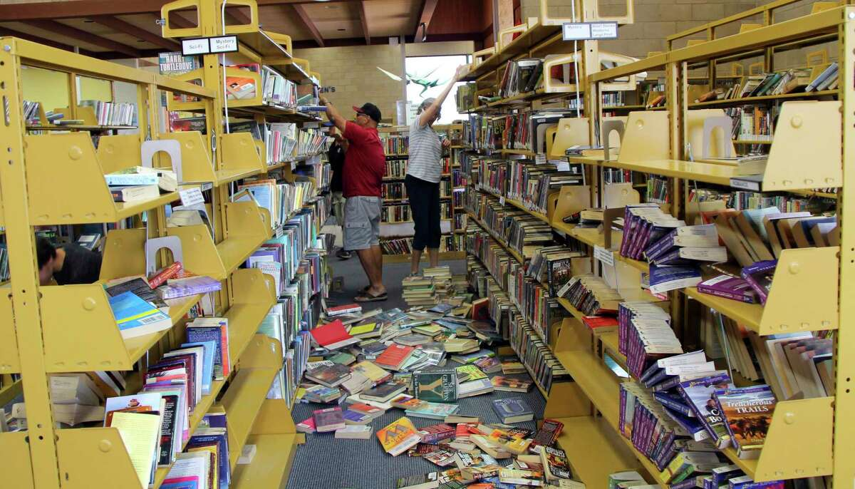 Some shelves are nearly empty as volunteers assist with cleanup at the Ridgecrest, Calif., branch of the Kern County Library on Friday, July 5, 2019, following a 6.4 magnitude earthquake that shook the region about 150 miles (240 kilometers) northeast of Los Angeles Thursday. Aftershocks from Southern California's largest earthquake in 20 years rumbled beneath the Mojave Desert on Friday as authorities tallied damage in the sparsely populated region. (Jessica Weston/The Daily Independent via AP)