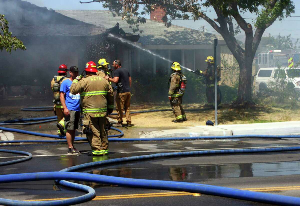 In this Thursday, July 4, 2019 photo, Kern County firefighters work to knock down a fire that severely damaged a home on South Sunland Street in Ridgecrest, Calif., following a 6.4 magnitude earthquake that shook the region about 150 miles (240 kilometers) northeast of Los Angeles. Aftershocks from Southern California's largest earthquake in 20 years rumbled beneath the Mojave Desert on Friday as authorities tallied damage in the sparsely populated region. (Jack Barnwell/The Daily Independent via AP)