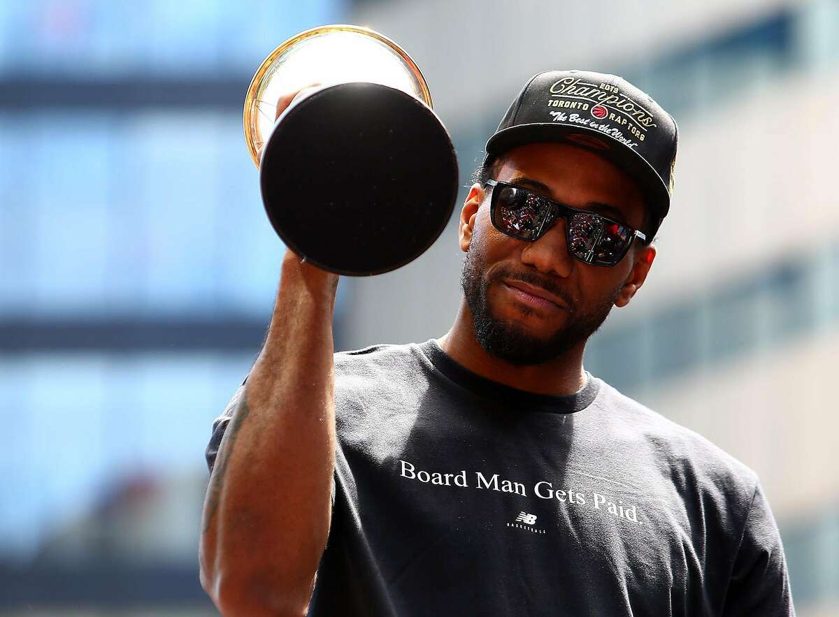 Kawhi Leonard of the Toronto Raptors holds the MVP trophy during the team's victory parade on June 17, 2019, in Toronto, Canada. (Vaughn Ridley/Getty Images/TNS) **FOR USE WITH THIS STORY ONLY**