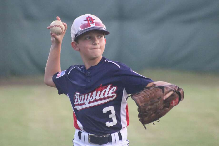 Bayside 10s left fielder Austin Goodfriend warms up with a teammate Friday night. His family told him to smile and he finally did, especially when he came up with Bayside's first hit to the outfield grass in the second inning. Photo: Robert Avery