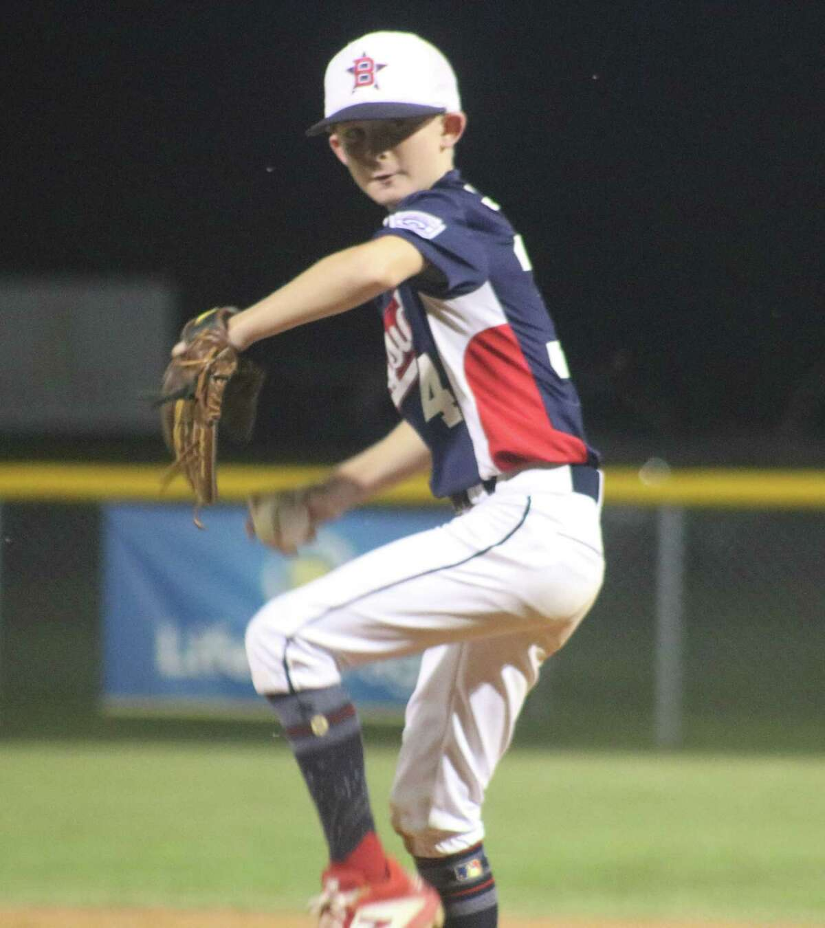 Bayside 10s starting pitcher Jason Cooper works on a batter in his final inning Friday night. Cooper received a no decision. He departed with the score 2-2. He scattered five hits, but two hit batters in the second inning forced in a tying run.