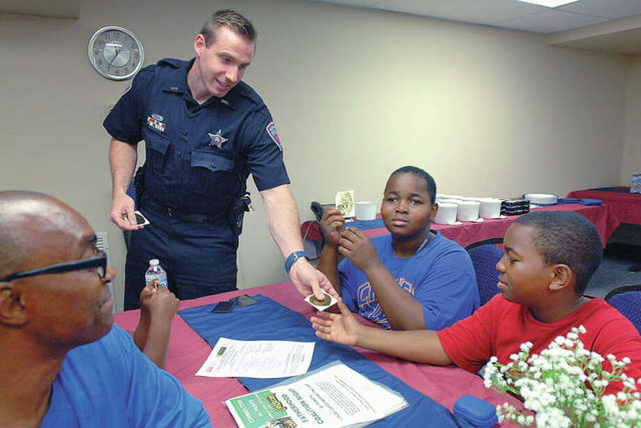 Bloomington police officer John Furmon talks with Fatherhood Coalition member Anthony Jones (from left) and his sons DeAnthony, 12, and Antone, 10, during a meeting at the Scott Early Learning Center in Bloomington. Photo: David Proeber | The Pantagraph (AP)
