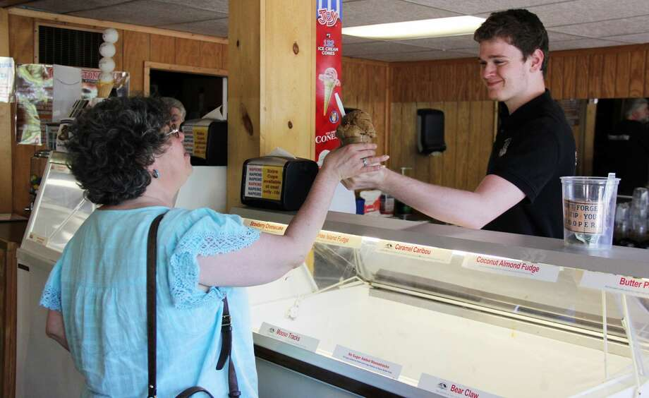 One of the many scoopers at Grindstone General Store hands a customer a bowl of their delicious homemade ice cream. The store has been scooping tasty ice cream for decades and feature a variety of unique flavors. Photo: Andrew Mullin/Huron Daily Tribune